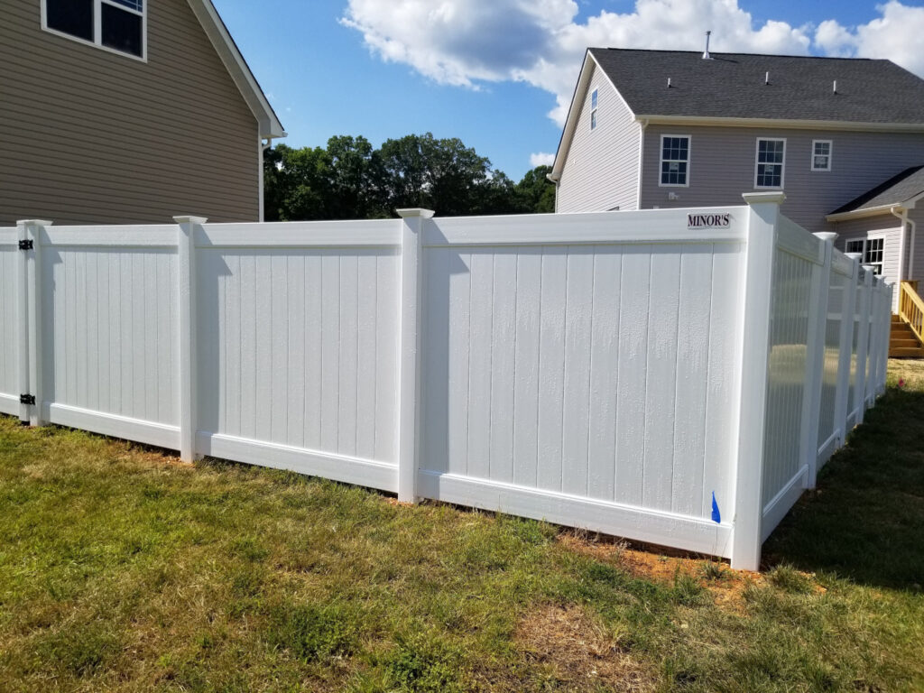 Six foot high white vinyl tongue and groove privacy fence featuring New England post caps.