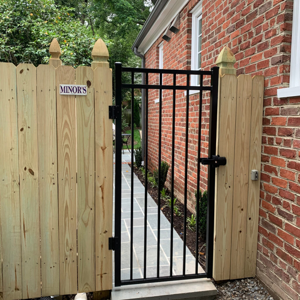 Six foot high wood privacy fence featuring french gothic posts and a series-a 3-rail commercial aluminum gate.