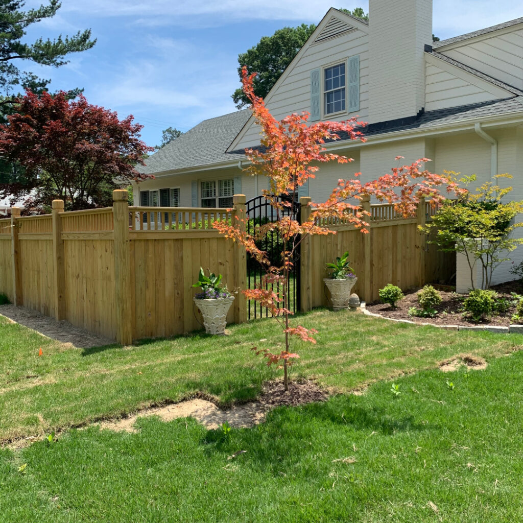 Six foot flat top picket, wood privacy fence. This fence features 6x6 beveled & notched posts and a commercial 3-rail aluminum arched gate.