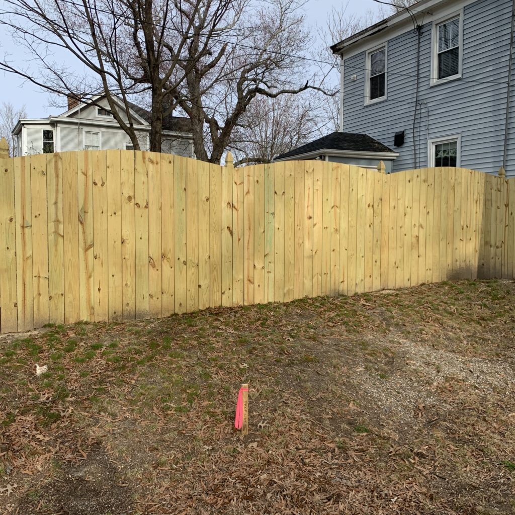 6 foot high convex wood privacy fence with French Gothic posts