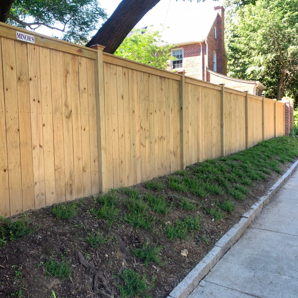 Six foot tall top cap and finish board fence with customer installed post caps.