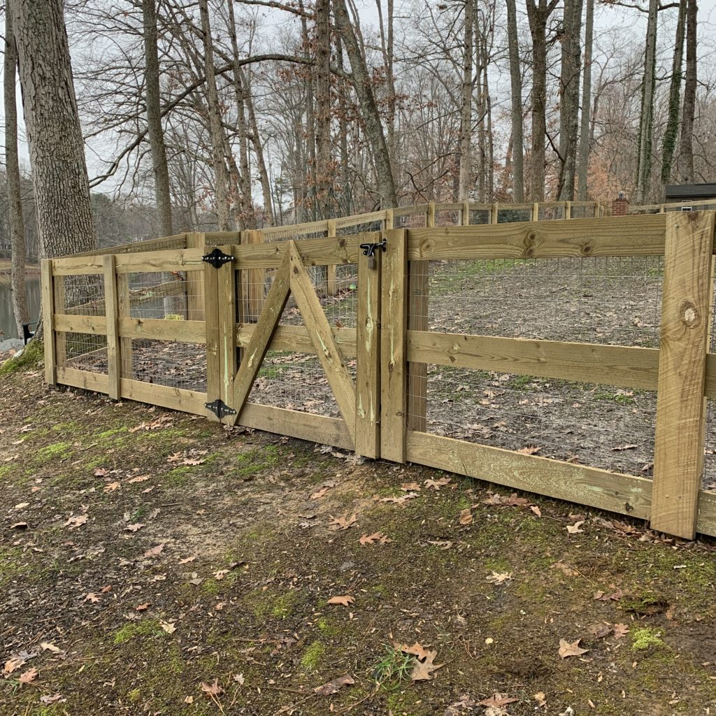 Horizontal board fence secured with welded wire and a locking gate.