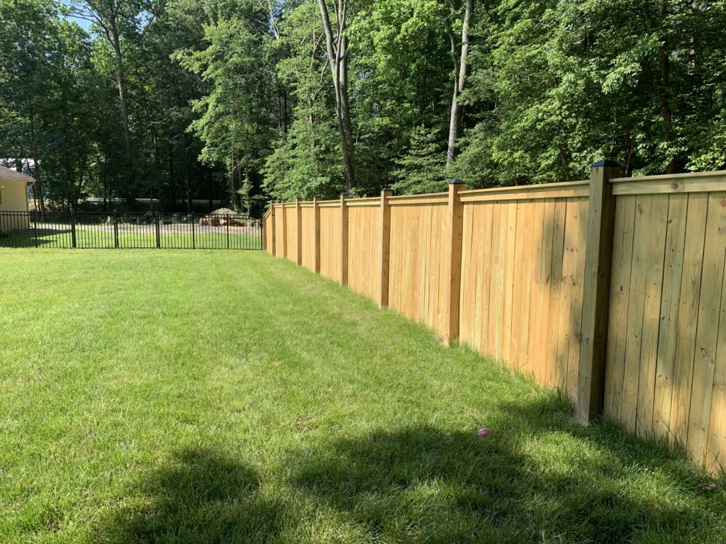 Top cap and finish board wood privacy fence tied to aluminum fencing